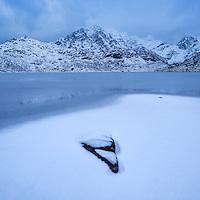HImmeltindan mountain peak rises over frozen Vikvatnet, Vestvågøy, Lofoten Islands, Norway