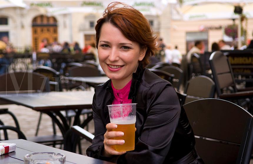 Attractive woman in city center having beer at outdoor cafe, Lviv Ukraine