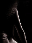 Sensual abstract closeup of a nude woman back with man hand on her waist, black and white body parts fine art