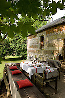 A table is laid for lunch on the shady open terrace of a converted gamekeeper's cottage in Normandy where a low stone wall is utilised for extra seating