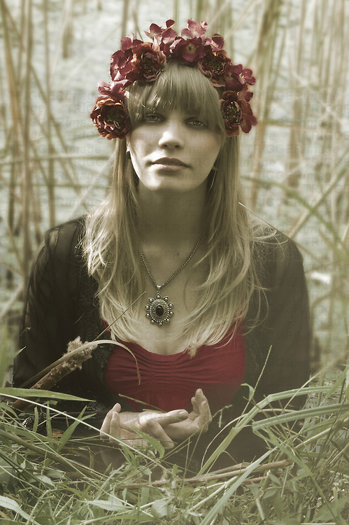 Photograph of a young caucasian woman with blonde hair, standing waist deep in a pond surrounded by foliage. She has a serene expression on her face and has her hands folded together. She has red flowers in her hair and is wearing a red dress with a black sheer jacket that is opened. Her necklace is a silver chain with a silver and black medallion.