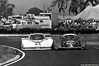 The Group 44 Jaguar XJR-5 004 elbows its way underneath the Grid Plaza S1 GA01/Ford in the 1983 event.