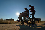 Delina Nleya gets a push from her daughter Nkazimulo, 16, on the street near her house in Bulawayo, Zimbabwe. Nleya suffered a spinal cord injury and uses a wheelchair provided by the Jairos Jiri Association with support from CBM-US.