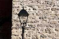 Black metal lantern with stone wall in background in Old Montreal, Quebec, Canada