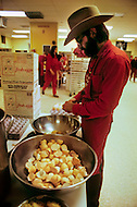 Wasco, Oregon, February 1984: Disciples of Bhagwan Rajneesh, preparing vegetarian meals in the community kitchen, which would be served in the lunchroom. Most of the food came from the community ranch.  Rajneeshpuram, was an intentional community in Wasco County, Oregon, briefly incorporated as a city in the 1980s, which was populated with followers of the spiritual teacher Osho, then known as Bhagwan Shree Rajneesh. The community was developed by turning a ranch from an empty rural property into a city complete with typical urban infrastructure, with population of about 7000 followers.