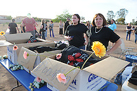 """Gilbert, Arizona – Friends and family of the Mederos Family gathered to hold a memorial for the four victims of the Gilbert Massacre occurred on May 2, 2012. According to Gilbert Police, Lisa Mederos, Amber Mederos, baby Lilly Mederos, and Jim Hiott (Amber's fiancé) were all killed by notorious white supremacist and Neo-Nazi Jason """"J.T."""" Ready before taking his own life. In this image, two women volunteers are in charge of selling t-shirts in memory of Lisa Mederos, Amber Mederos, Lilly Mederos and Jim Hiott as a fundraiser for the survivors. Photo by Eduardo Barraza © 2012"""