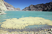 Kawah Ijen Volcano, Java, Indonesia showing a sulfurous raft floating on the surface of a turquoise-colored acidic crater lake.