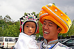 Asia, China, Kunming. Ethnic minority father holds baby, both in traditional headwear.