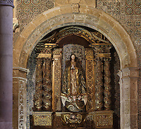 Painted statue of St Ursula, 17th century, in a niche with gilded columns and walls covered with 16th century Mudejar tiles, in the Old Cathedral of Coimbra, or Se Velha de Coimbra, a 12th century Romanesque Roman Catholic cathedral in Coimbra, Portugal. The cathedral was designed by Master Robert, a French architect, with the works overseen by Master Bernard and Master Soeiro. It was reworked in the 16th century, with the addition of tiled decoration, a portal and Renaissance chapel. The city of Coimbra dates back to Roman times and was the capital of Portugal from 1131 to 1255. Its historic buildings are listed as a UNESCO World Heritage Site. Picture by Manuel Cohen