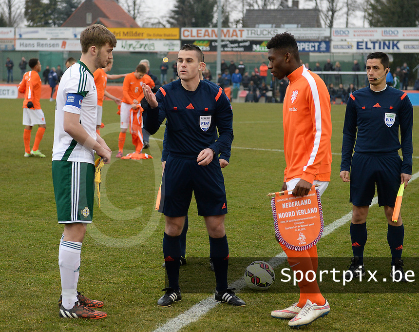 20150314 - GENDT , NETHERLANDS  : Serbian Referee Milan Ilic pictured flipping the coin in front of Northern-Ireland captain Dylan King (left) and Dutch Captain Timothy Fosu-Mensah (right) during the soccer match between Under 17 teams of  The Netherlands and Northern Ireland , on the second matchday in group 3 of the UEFA Elite Round Under 17 at De Bataven Stadion , Gendt , The Netherlands . Saturday  14 th March 2015 . PHOTO DAVID CATRY