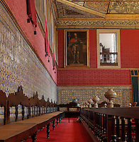 The Great Room of Acts, or Sala dos Capelos, or Red Room, decorated in the 17th century by master builder Antonio Tavares and reworked in the 18th century, with ceiling panels by Jacinto Pereira da Costa, part of the University of Coimbra in the royal palace or Paco Real, Coimbra, Portugal. Originally the throne room of the palace, and now used for University ceremonies, the room houses many large paintings of successive Kings of Portugal. The University of Coimbra was first founded in 1290 and moved to Coimbra in 1308 and to the royal palace in 1537. The buildings are listed as a historic monument and a UNESCO World Heritage Site. Picture by Manuel Cohen