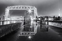 &quot;Aerial Spring Reflections&quot; (monochrome)<br /> The ice has vanished, but rain puddles and fog have reappeared, and the pier gates are open -- sure signs of Spring in Duluth! The iconic Aerial Lift Bridge casts bold reflections in the puddles.