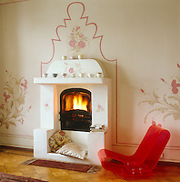 A red Perspex chair infront of a simple fireplace outlined with a stencil