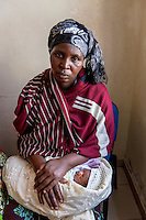 Africa, DRC, Democratic Republic of the Congo, Goma, Lake Kivu, Hotel Cap Kivu. Global Fund for Women. PAIF project. Dusabe Tumaini (32 years), Rehema (baby, one week). I&rsquo;m from Masis in the Congo, where 90% of the women are raped and many people are killed everyday. There&rsquo;s no presence of government there, only bandits, locals carrying guns. I was married with 7 children. One day I went into the forest to collect firewood and I was attacked and raped by four men in military uniforms. They left me to die but some local villagers found me and brought me to a hospital. I didn&rsquo;t want anyone to know I had been raped but it was soon discovered that I was pregnant. When my husband found out I was raped he ran away and left me with the 7 children. He was afraid of AIDS. And when he found out I was pregnant he didn&rsquo;t want to raise someone else&rsquo;s baby. Eventually his family and our pastor talked him into returning. Rehema was born a week ago. Now we say we have 7 children and this one. My husband said at least it&rsquo;s girl, she can be useful and work and bring in cows when she marries. <br /> PAIF has helped to move away from that terrible area and we now live in their temporary housing in Goma. Because we&rsquo;re displaced people the children don&rsquo;t go to school.  My life changed that day I went to collect firewood in the forest.