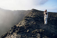 Tourist taking a picture near the smoke billowing from the crater of Yasur Volcano, Tanna Island, Vanuatu.