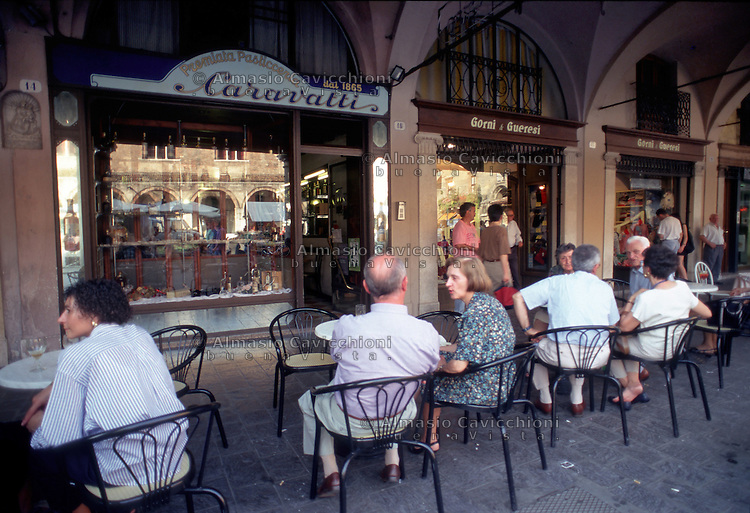 Mantova, Via Broletto, gente seduta ai tavolini della storica pasticceria Caravatti sotto i portici.<br /> Mantua, Via Broletto, People sitting at an outdoor cafe in the arcades.