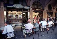 Mantova, Via Broletto, gente seduta ai tavolini della storica pasticceria Caravatti sotto i portici.<br /> Mantua, Via Broletto, People sitting at an outdoor cafe in the arcades.