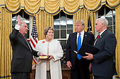 US President Donald J. Trump (2-R) watches as Rex Tillerson (L) is sworn-in as Secretary of State by US Vice President Mike Pence (R), beside Tillerson's wife Renda St. Clair (2-L), in the Oval Office of the White House in Washington, DC, USA, 01 February 2017. Tillerson was confirmed by the Senate, 01 February, in a 56-to-43 vote to become the nation's 69th Secretary of State.<br /> Credit: Michael Reynolds / Pool via CNP