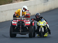 Jul. 18, 2014; Morrison, CO, USA; NHRA pro stock motorcycle rider Steve Johnson catches a ride with a Safety Safari quad during qualifying for the Mile High Nationals at Bandimere Speedway. Mandatory Credit: Mark J. Rebilas-