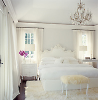 In the master bedroom all the furniture is lacquered shiny white including the ornately carved headboard, beside cabinet and side table