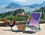 A terrace in Menaggio with a small wooden table, blue and pink chair, and straw basket with a view of Lake Como, Italy and the town of Bellagio in the background