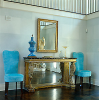 A pair of contemporary chairs upholstered in turquoise velour flanks an antique gilded console table in the entrance hall