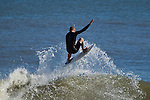 Surfer getting in the air on a wave in Folly Beach