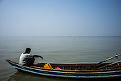 A fisherman waits on the boat while fishing using the stow nets in Damin Naung village in Pyapon district of Myanmar.