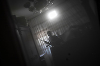 In this Thursday, Nov. 01, 2012 photo, a rebel fighter silhouette is reflected on a mirror inside a bedroom as he watchs over on his enemy's position during clashes in the nearby Karmal Jabl battlefield in Aleppo, the Syrian's largest city. (AP Photo/Narciso Contreras).
