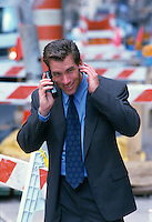 businessman having trouble hearing on a cellphone while outside in NYC
