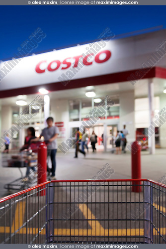 Person with a shopping cart entering COSTCO store, membership warehouse club chain, in the evening. Artistic out-of-focus blur. Scarborough, Toronto, Ontario, Canada 2014.