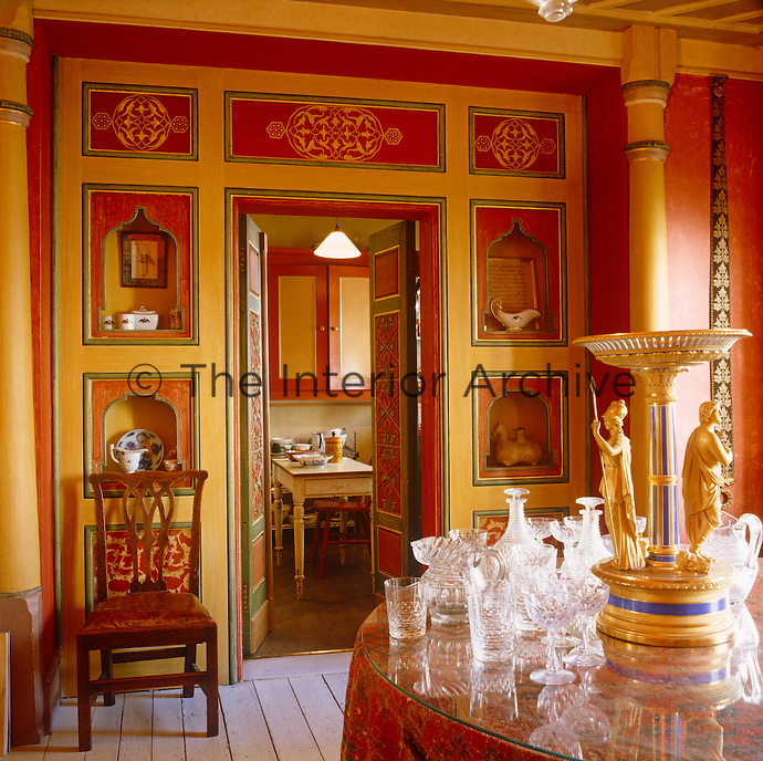 In this London dining room wooden panellling has been hand-painted a golden yellow and bright orange to resemble an Indian palace