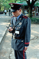 China. Province of Zhejiang. Hangzhou. A private security guard reads a new sms message on his mobile phone. © 2004 Didier Ruef