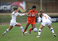 COLLEGE PARK, MD - OCTOBER 28, 2012:  Danielle Hubka (34) and Alex Reed (7) of the University of Maryland close in on Blake Stockton (29) of Miami during an ACC  women's tournament 1st. round match at Ludwig Field in College Park, MD. on October 28. Maryland won 2-1 on a golden goal in extra time.