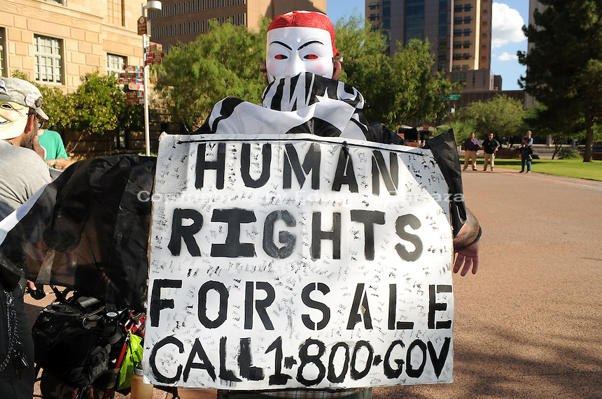 "Phoenix, Arizona. September 17, 2012 - A small crowd of demonstrators in Phoenix, Arizona gathered to mark one year since the beginning of the Occupy Movement that opposes Wall Street and large corporations that represent the one percent who control wealth in the United States. In this photograph, an activist who took part of the march and protest wears a sign on his back that reads ""Human Rights For Sale Call 1-800-Gov,"" to express his feeling toward the U.S. government. Photo by Eduardo Barraza © 2012"