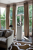 A sculpture on a plinth in front of the floor-to-ceiling living room windows that lead out to the garden