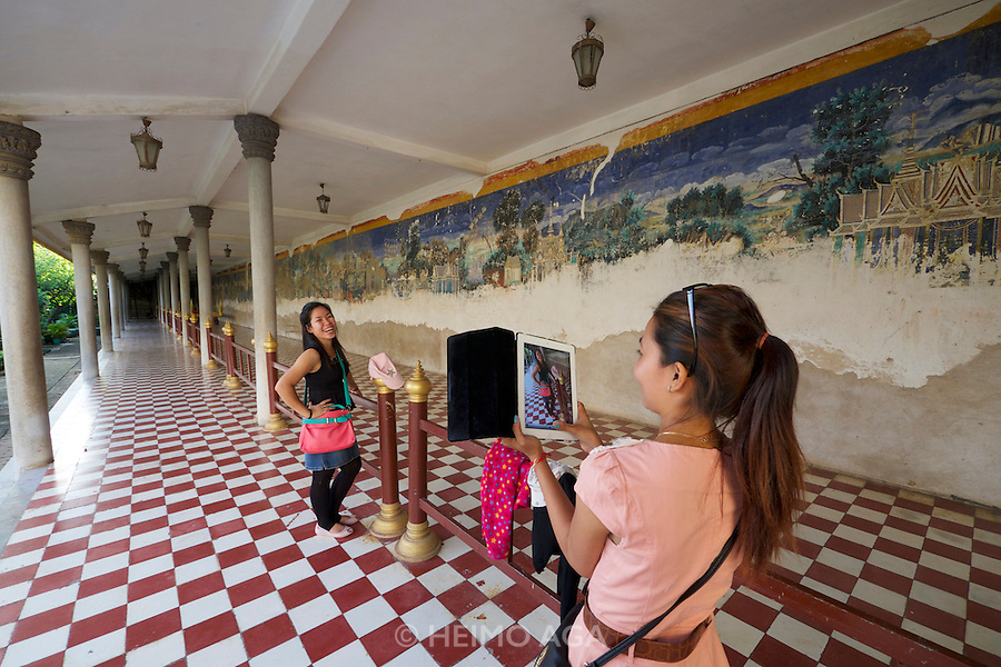Phnom Penh, Cambodia. Royal Palace. Silver Pagoda Compound. Tourists making souvenir photos with the Reamker (Ramayana) frescoes on the surrounding wall.
