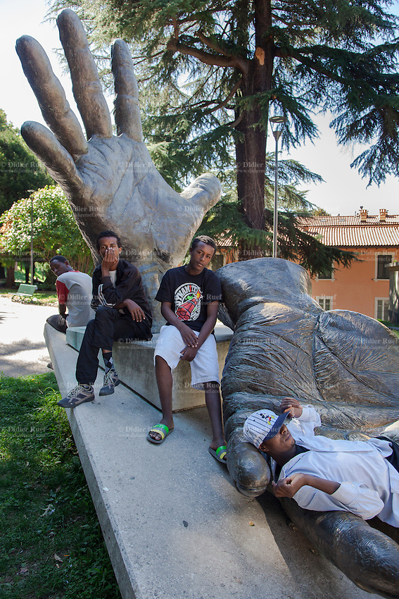 Italy. Lombardy Region. Como. Homeless african migrants living in the park below the San Giovanni railway station. Four young men from Eritrea sit on a memorial sculpture to disabled war soldiers (Unione Nazionale Mutilati per Servizio). The sculptor is Massimo Clerici. 10.08.2016 © 2016 Didier Ruef