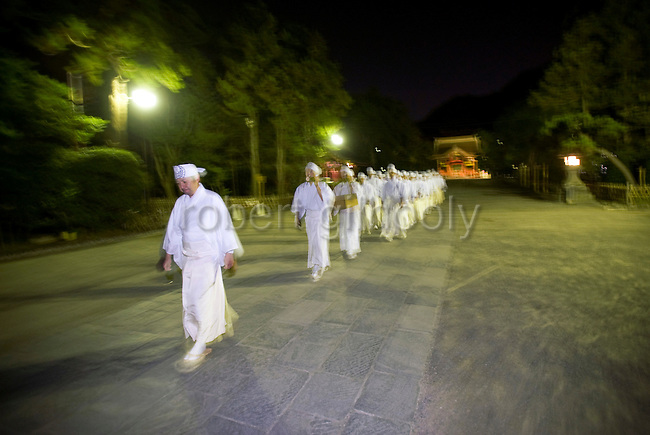 """Shrine priests and officials make their way along the Dankazura approach road of the Tsurugaoka Hachimangu shrine on their way to Yuhigahama beach to perform a rite known as """"hamaorisai"""" at the start of the 3-day Reitaisai festival in Kamakura, Japan on  14 Sept. 2012.  During the ritual the priests collect seaweed from the sea and decorate the shrine with the rewards of their early morning endeavors. Photographer: Robert Gilhooly"""
