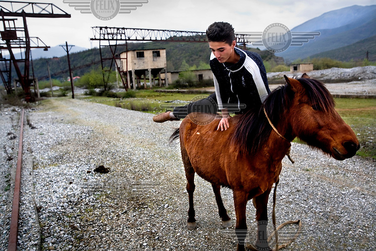 A boy jumps onto his horse in a field near an old, disused concrete factory.