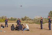 Police helicopter patrols over officers detaining illegal migrants after crossing the razor wire fence on the border between Serbia and Hungary near Roszke (about 174 km South of capital city Budapest), Hungary on September 15, 2015. ATTILA VOLGYI