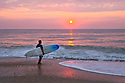 NC00516-00...NORTH CAROLINA - Surfer at sunrise on the south end of Wrightsville Beach.
