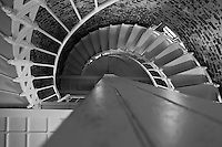 A view from the bottom of the stairway leading to the top of Point Sur Light Station's lighthouse's lantern room.  I'm a total sucker for lighthouse stairways ? the white iron stairway contrasts beautifully with the wooden central beam and brick exterior (with light streaming in through a window).