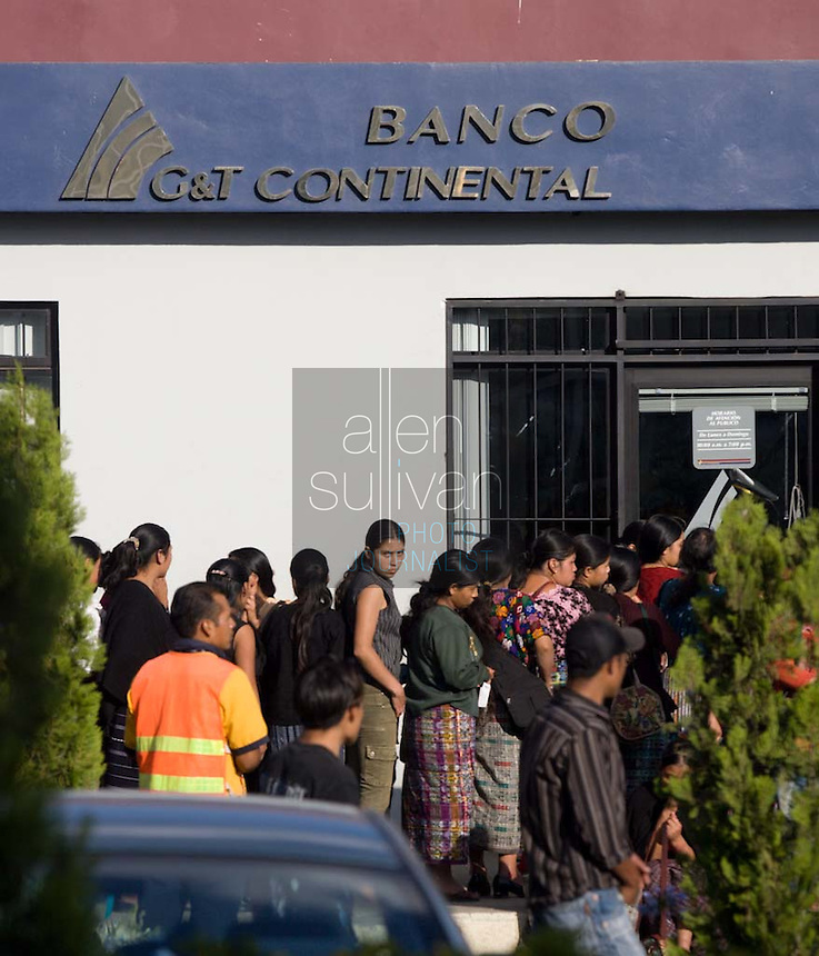 Bank customers, including workers from Legumex, a vegetable and fruit company that exports to the United States, wait to cash checks in Chimaltenango, Guatemala on Thursday, March 8, 2007, a payday.
