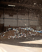 """April 4, 2012. Durham, NC.. Trash is dumped by truck into the warehouse where it is pushed into a compactor and formed into """"trash logs"""" for transfer to a private landfill in Montgomery County, NC.. Photographs of the Durham waste transfer station located at 2115 Eat Club Blvd."""