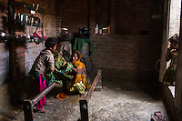 Sultana's mother and sisters set up the saree frame as Sultana (not in picture) starts to embellish a saree in her home in Varanasi, Uttar Pradesh, India on 23 November 2013. Sultana was enticed by a trafficker on the pretext of marriage and was raped repeatedly as he filmed her, using the film to blackmail her as he sold her to another trafficker for INR50000 (USD800). Guria has since put almost all of her traffickers into jail, and has provided her with a grant for livelihood support, which she used to start her saree embellishment business.