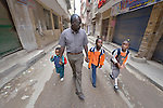 Abdel Karim, a refugee from the Darfur region of Sudan, walks his children to school in the morning through the streets of Cairo, Egypt. Karim and his wife have both taken adult education classes provided by St. Andrew's Refugee Services, which is supported by Church World Service. His children, from left, are Ahmed, 4;  Ziad, 9; and Dana, 7.