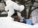 An artists works on his Ice sculpture in Odori Park.These are not traditional Frosty the Snowmen, but huge carved and chiseled Samurai Warriors, Buddhists gods, historical heroes of fairy tales and Walt Disney characters. Some stand as big as buildings. Chiseled out of tons of packed snow, the sculptures are the pride and job of the residents of Sapporo, Japan, who hosts the world famous Ice and Snow Sculpture Festival for five days in early February.Themes of the sculptures are picked from Kabuki stages, historical characters or fairy tales. (Jim Bryant Photo).....