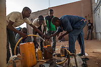 AGADEZ, NIGER &mdash; <br /> Migrants, housed in what is commonly referred to as a &quot;ghetto&quot;, fill up their water containers as they prepare for night fall before packing their belongings on the small pick-up trucks that will drive them through the desert on their way to Libya. Each migrant carries two gallons of water for the three day journey through the Sahara desert.