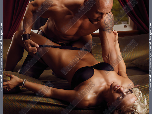 Muscular man and a woman making love in bed